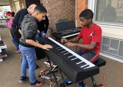 Attendees playing the piano at CMS Halloween Parade Open House