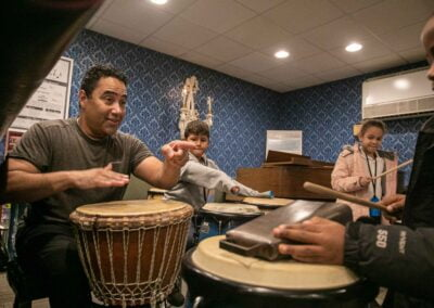Kids receiving drum lessons from CMS teacher Daniel Gonzalez as part of the Allentown Newcomer Academy Field Trip to CMS