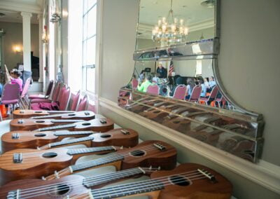 Photo of a line of ukuleles arranged in a row on a table in front of a mirror