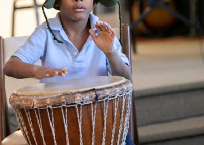 Photo of a child playing the drums at the Allentown Newcomer Academy Holiday Concert at CMS