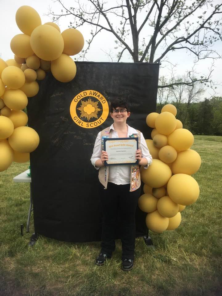 Sammi Ciommo receives Girl Scout Gold Award in Outdoor Ceremony black background gold balloons holding certificate